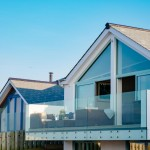 Tregoose Polzeath contemporary home white exterior box design gable window balcony designed by The Bazeley Partnership, architects in Cornwall and Devon